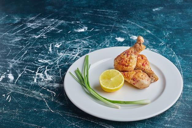 레몬 흰 접시에 튀긴 매운 닭 다리.
