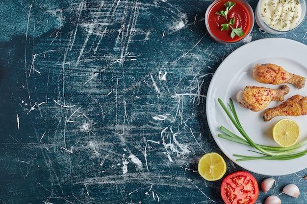 Coscia di pollo piccante fritta in un piatto bianco con il limone.