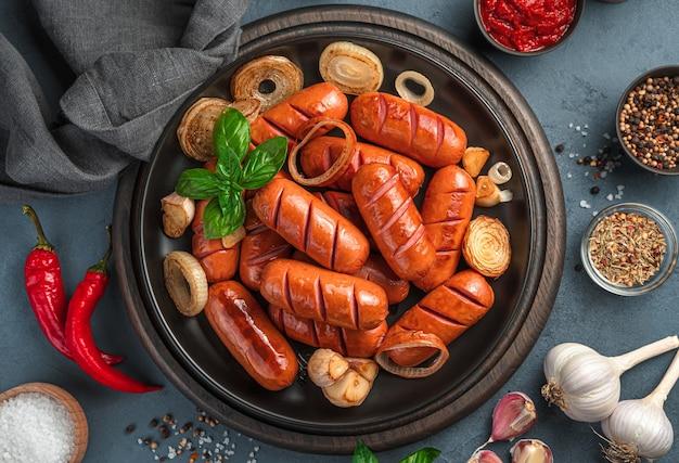회색 파란색 배경에 양파, 마늘, 바질을 곁들인 튀긴 매운 소시지. 확대.