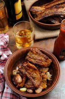Жареная острая свиная грудинка с чесноком и кетчупом к пиву вертикальный снимок