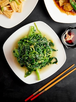 Fried spinach and soy sauce on table