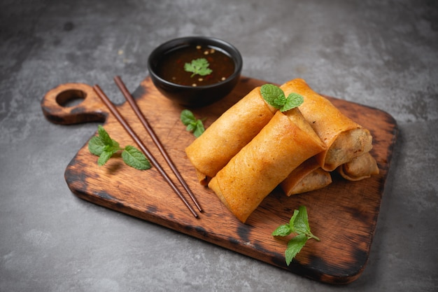Fried spring rolls on cutting board.