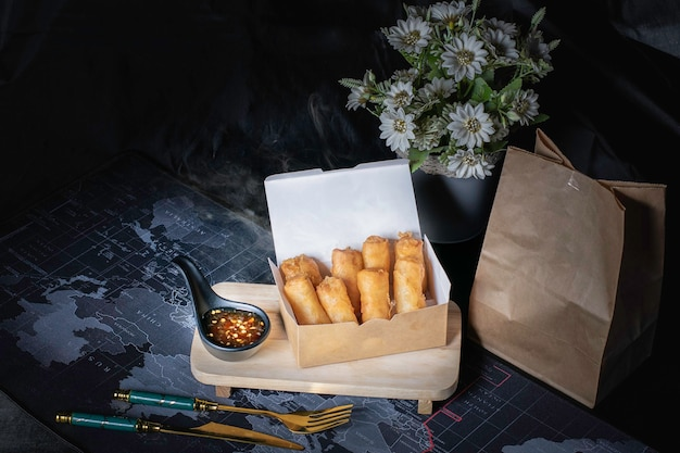 Fried spring rolls and dipping sauce in brown paper box
