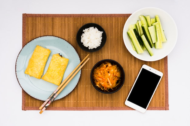 Fried spring rolls; salad; boiled rice and sliced zucchini with cell phone over placemat
