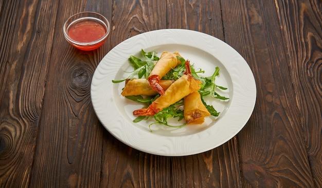 エビ、新鮮なルッコラのサラダ、甘いチリソースを添えた揚げ春巻きを、木製のテクスチャーテーブルの上に白いプレートでお召し上がりいただけます。平面図フラットレイ、コピースペースアジア料理のコンセプト