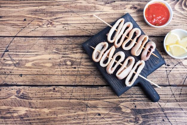 イカフライの串焼きにトマトソースとレモンを添えて。暗い木製の背景のコピースペース。上面図。