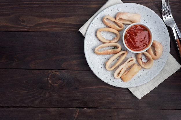 Fried squid rings with tomato sauce and lemon. dark wooden background copy space. top view.