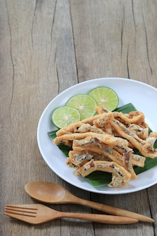 Fried squid of thai seafoods in the white dish on wood floor.
