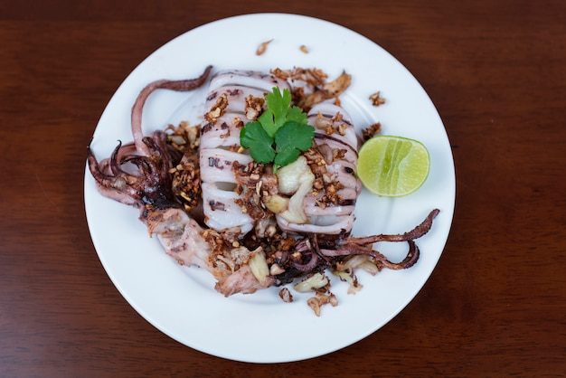 Fried squid with garlic, lemon on white plate on a wooden background.