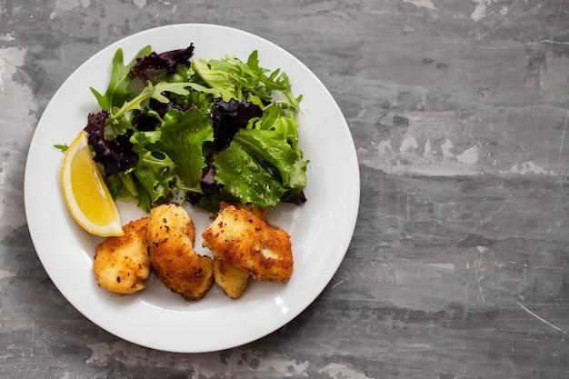 Жареный кальмар с салатом и лимоном на белой тарелке