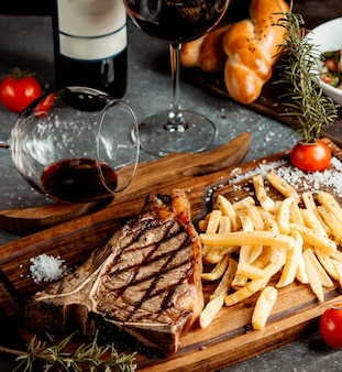 Fried steak with french fries on wooden board