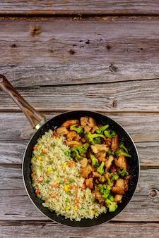 Жареный кисло-сладкий цыпленок с вареным рисом. вид сверху.