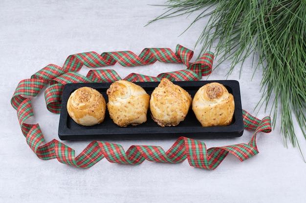 Жареные сладкие булочки на черной тарелке с лентой. фото высокого качества
