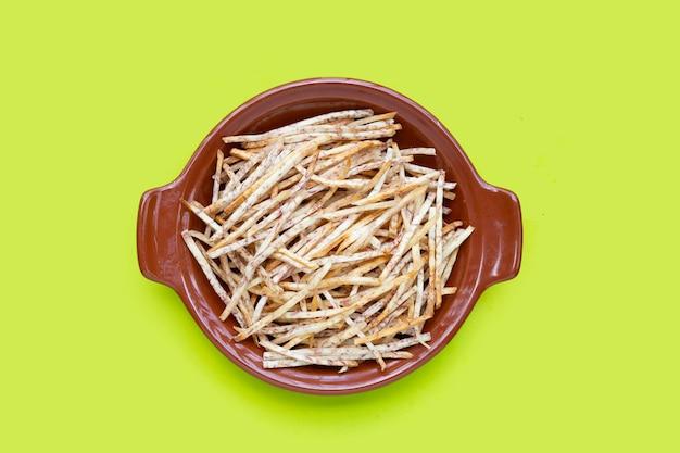 Fried taro sticks in bowl on green background.