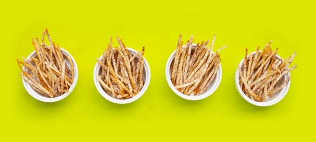 Fried taro sticks on green background.
