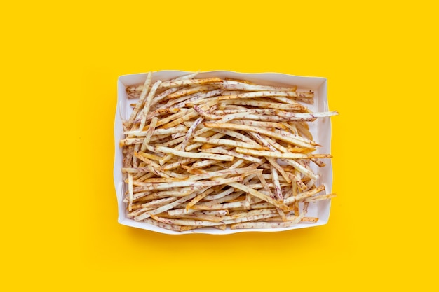 揚げ里芋は黄色の背景の紙箱に固執します。