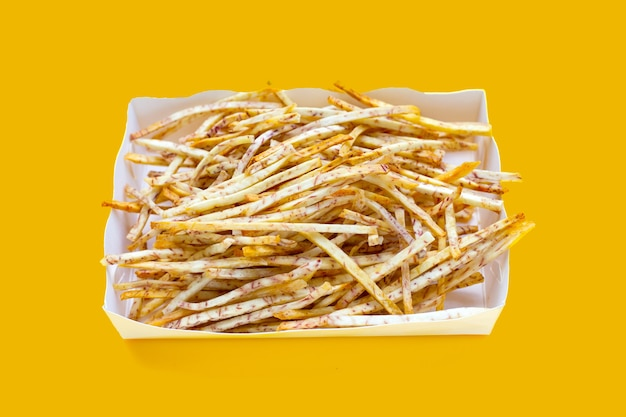 Fried taro sticks in paper box on yellow background.