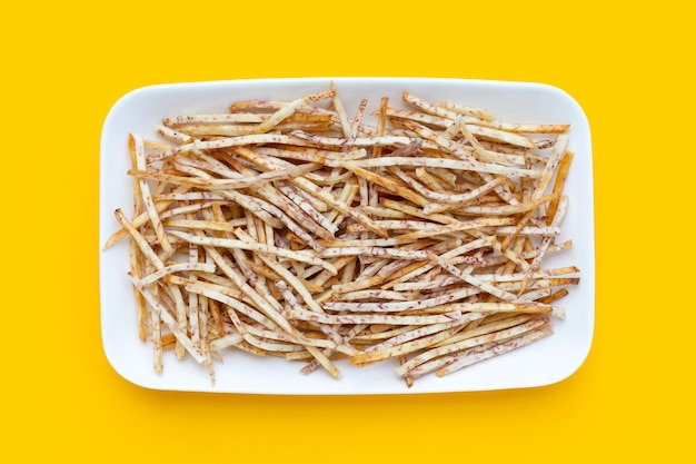 Fried taro sticks in white plate on yellow background.