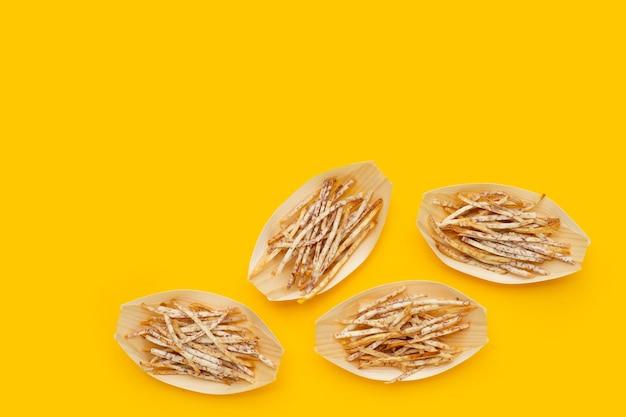 Fried taro sticks on yellow background.
