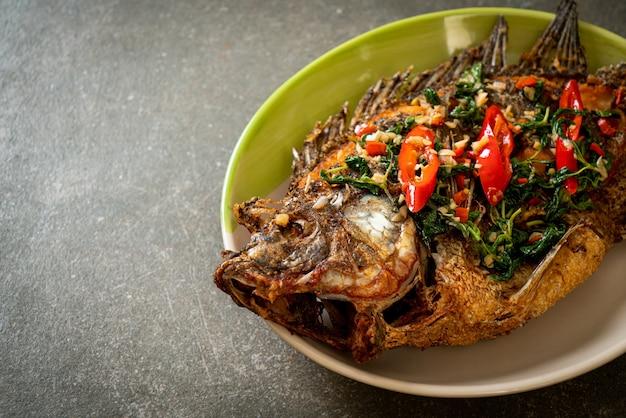 Жареная рыба тилапия в чесночном соусе с базиликом и чили сверху - домашний стиль еды