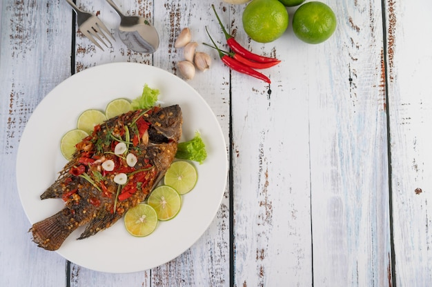 Fried tilapia with chili sauce,  lemon salad and garlic on a plate on a white wooden background
