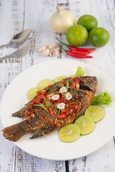 Fried tilapia with chili sauce,  lemon salad and garlic on a plate on a white wooden table.