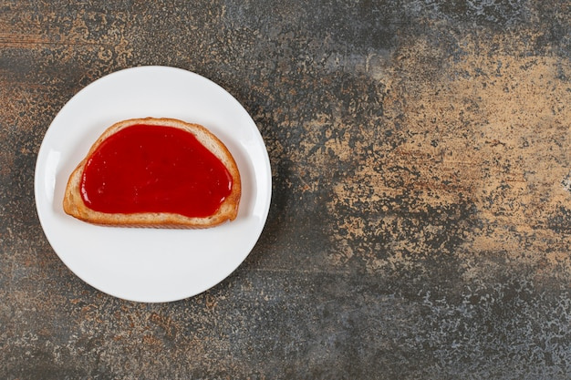 흰색 접시에 딸기 잼 튀긴 토스트.