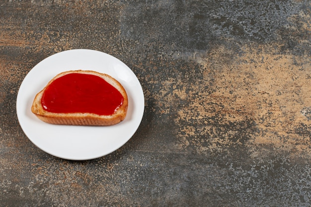 Fried toast with strawberry jam on white plate.