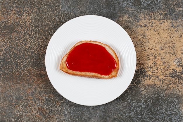 Pane tostato fritto con marmellata di fragole sul piatto bianco.