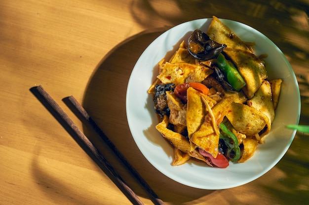 Жареный тофу в кисло-сладком соусе с сычуаньским перцем и овощами в белой тарелке. китайская кухня