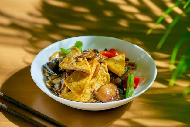 Жареный тофу в кисло-сладком соусе с сычуаньским перцем и овощами