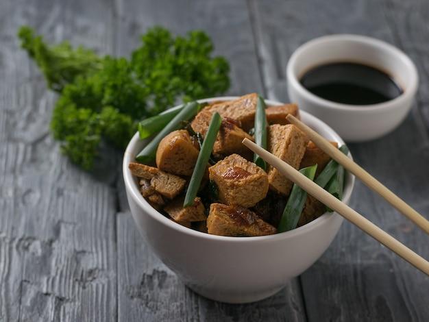 Жареный тофу, петрушка и деревянные палочки на столе. вегетарианское азиатское блюдо.