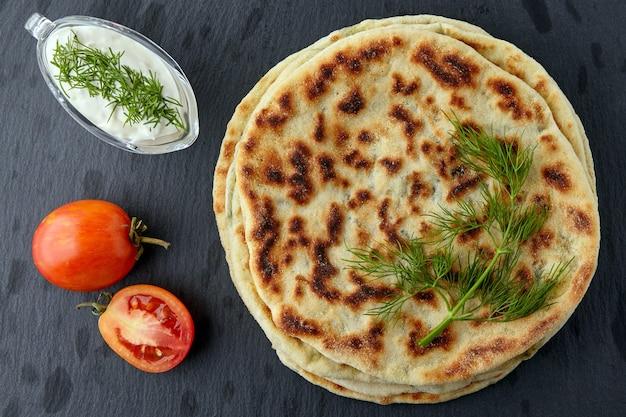 치즈와 허브, 요구르트 소스를 곁들인 튀긴 토르티야는 어두운 돌 탁자에 있는 하얀 접시에 있습니다. 평면도. 플랫 레이