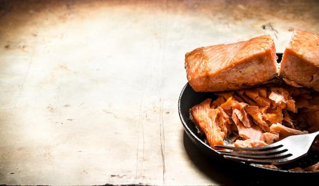 皿にフォークで揚げたマス。古い素朴な背景に。