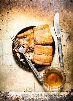 古い素朴なテーブルの上のフォークでプレートで揚げたマス。