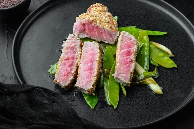 참깨 튀김 참치 스테이크, 봄 양파와 설탕 스냅 완두콩 세트, 접시에, 검은 돌 위에