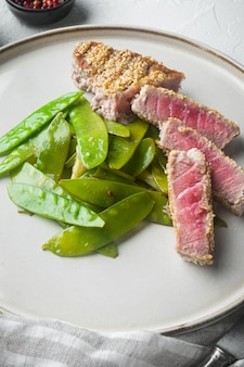 참깨 튀김 참치 스테이크, 봄 양파와 설탕 스냅 완두콩 세트, 접시에, 흰 돌에