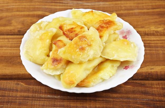 Жареные вареники с картофелем на тарелке.