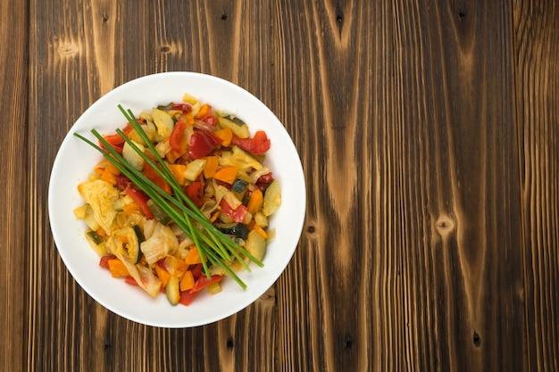 Жареная овощная смесь с кабачками, сладким перцем, помидорами черри, луком крупным планом. ресторан, где подают вегетарианские блюда из нарезанных кубиками вареных овощей и зелени