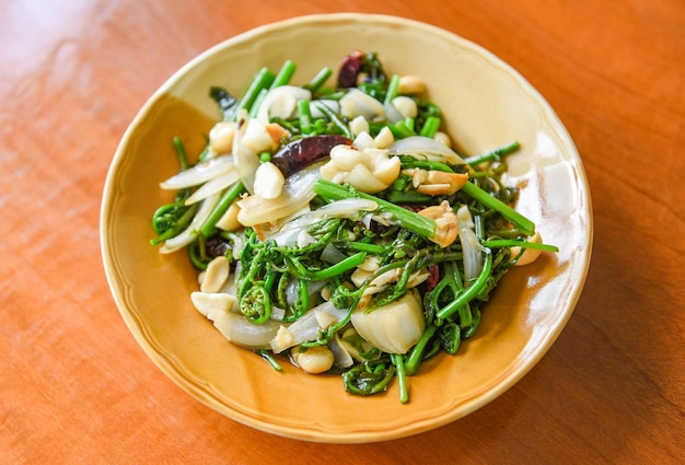 Fried vegetables - stir fry paco fern with macadamia nuts on top on white plate
