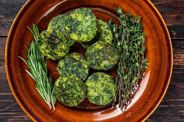 Жареные вегетарианские котлеты из овощных гамбургеров с брокколи на деревенской тарелке