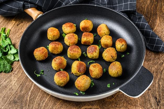 Жареные вегетарианские шарики фалафеля из приправленного специями нута на сковороде. деревянный фон. вид сверху.