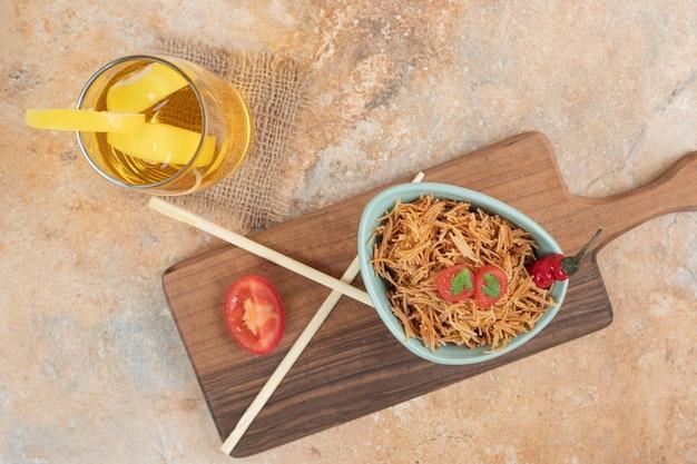 Жареная вермишель с помидорами и стаканом сока на деревянной доске