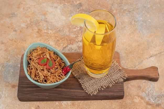 Жареная вермишель с помидорами и стаканом сока на деревянной доске.
