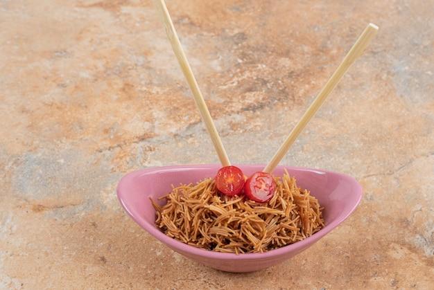 ピンクのボウルに箸でトマトと春雨を炒めた。