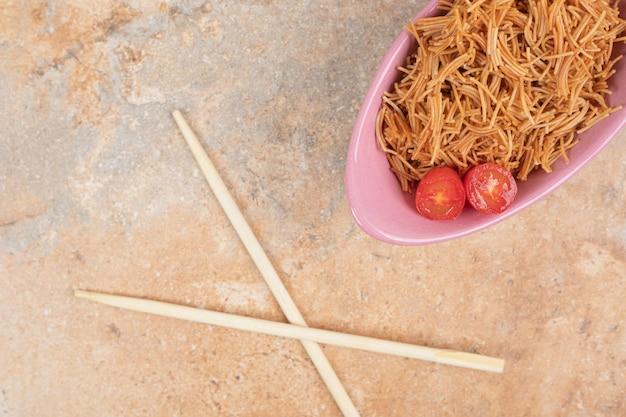 Жареная вермишель с помидорами в розовой миске с палочками для еды.