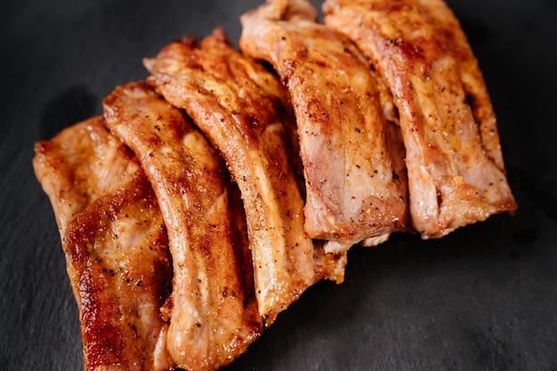 돌 검정 배경에 유리 베이킹 시트에 향신료 돼지 갈비와 함께 튀긴. 집에서 구운 고기. 야외 파티.