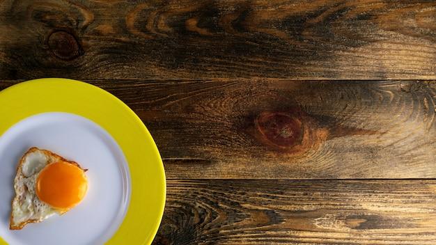 Жареный желток на круглой керамической тарелке с желтым краем на грубой деревянной поверхности
