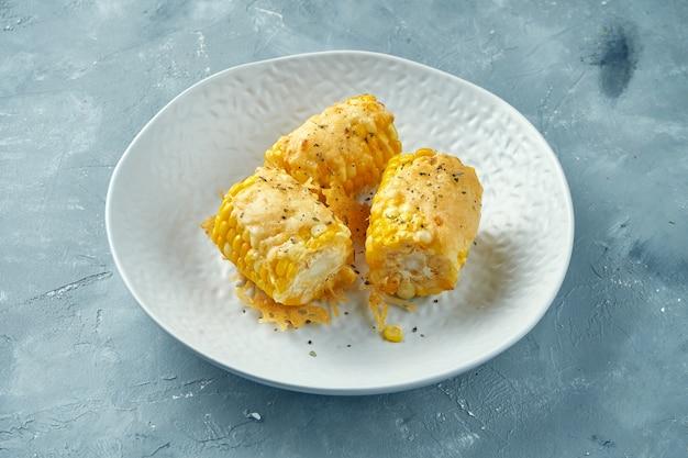 향신료와 흰 그릇에 녹은 치즈와 함께 튀긴 젊은 옥수수. 옥수수에 버터를 바른 구운 옥수수