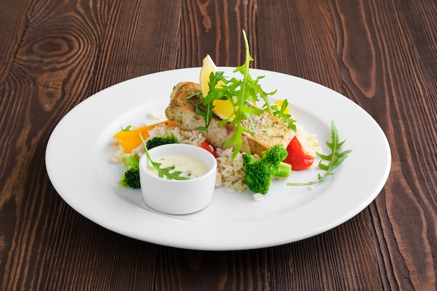 Fried zander with rice, bell pepper and arugula served with mayonnaise sauce on dark wooden table